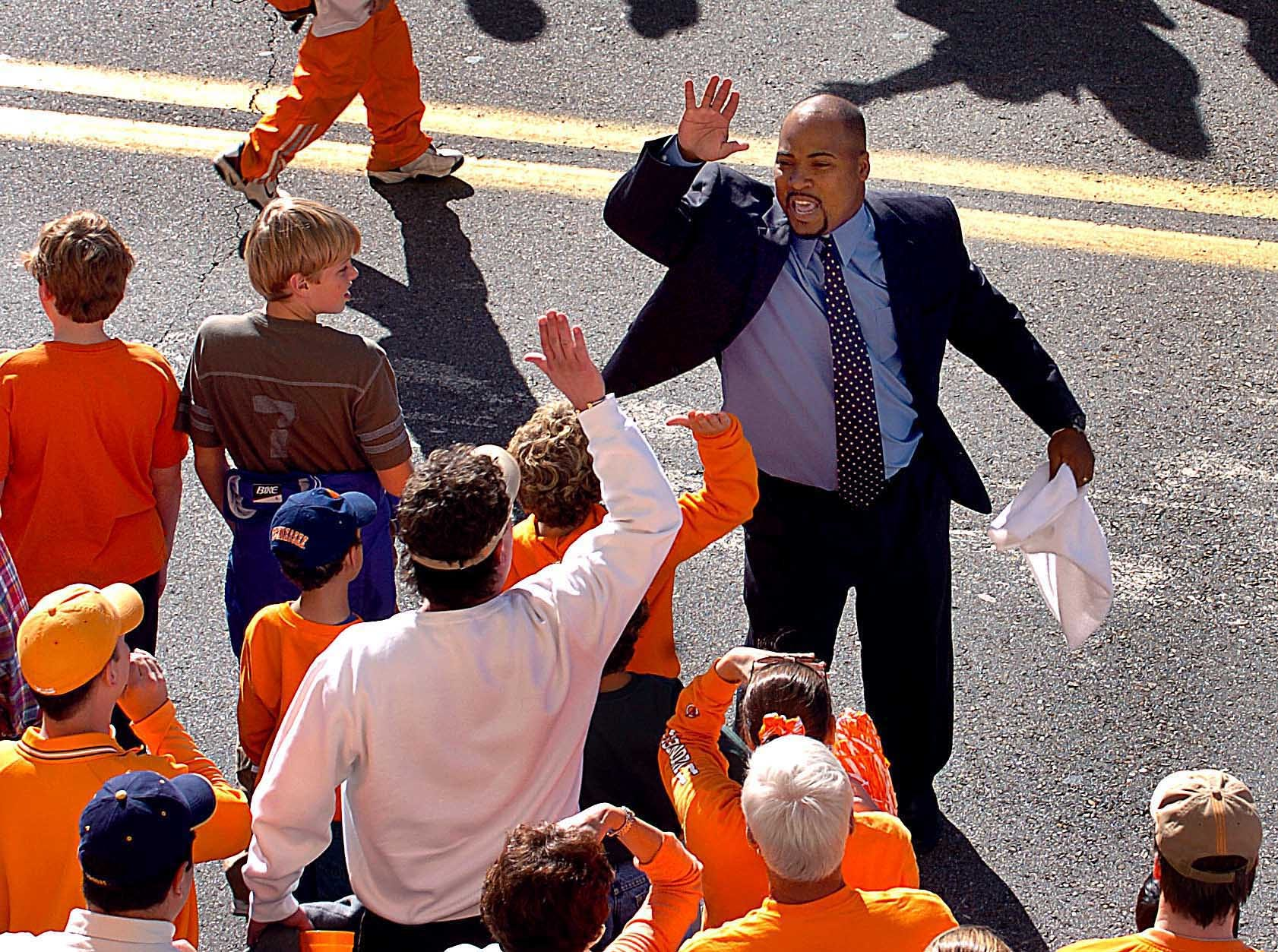gameday43.MP#2442 - 1:23:09 Saturday - Assistant football coach Trooper Taylor gives enthusiastic high-fives to fans as he walks along with his players in the Vol Walk.  11/6/2004 (Trooper_6769) MICHAEL PATRICK/NEWS SENTINEL STAFF