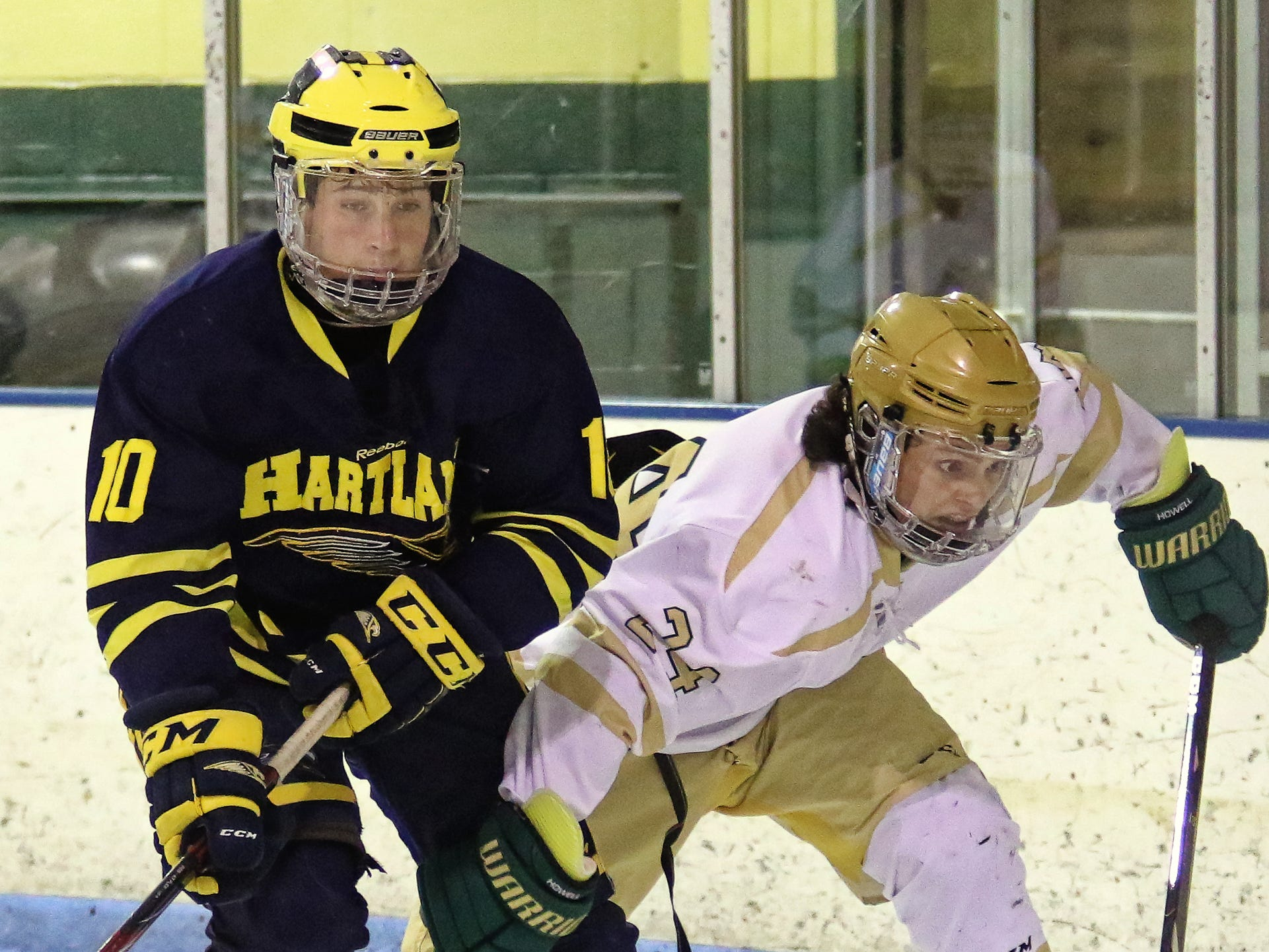 Hartland's Adam Pietila (10) and Howell's Brent Wolf chase down a puck in Hartland's 7-1 victory on Tuesday, Jan. 15, 2019.