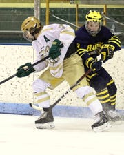Hartland's Bennie Tervo (right) and Howell's Nolan Schick battle along the boards on Tuesday, Jan. 15, 2019.
