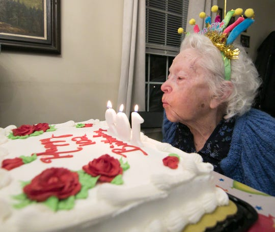 102-year-old Cecilia Spalding blows out her candles in a birthday party held for her at Blue Heron Pond Adult Foster Care Tuesday, Jan. 15, 2019.