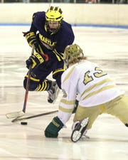 Hartland's Max McIllmurray carries the puck while defended by Howell's Steven Miller on Tuesday, Jan. 15, 2019.