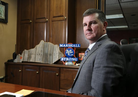 Trent Lovett, Marshall County Schools superintendent, sits in his office. Behind him are mementos that were given to him in remembrance of the Marshall County High School shooting last year. Jan. 14, 2019