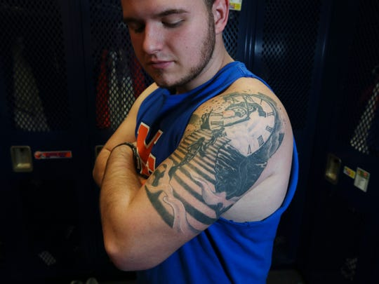 Devon Evans, 17, a Marshall County High School football player who was shot during last year's school shooting, has a tattoo on his bicep that symbolizes the two students who were killed ascending to heaven. Jan. 14, 2019