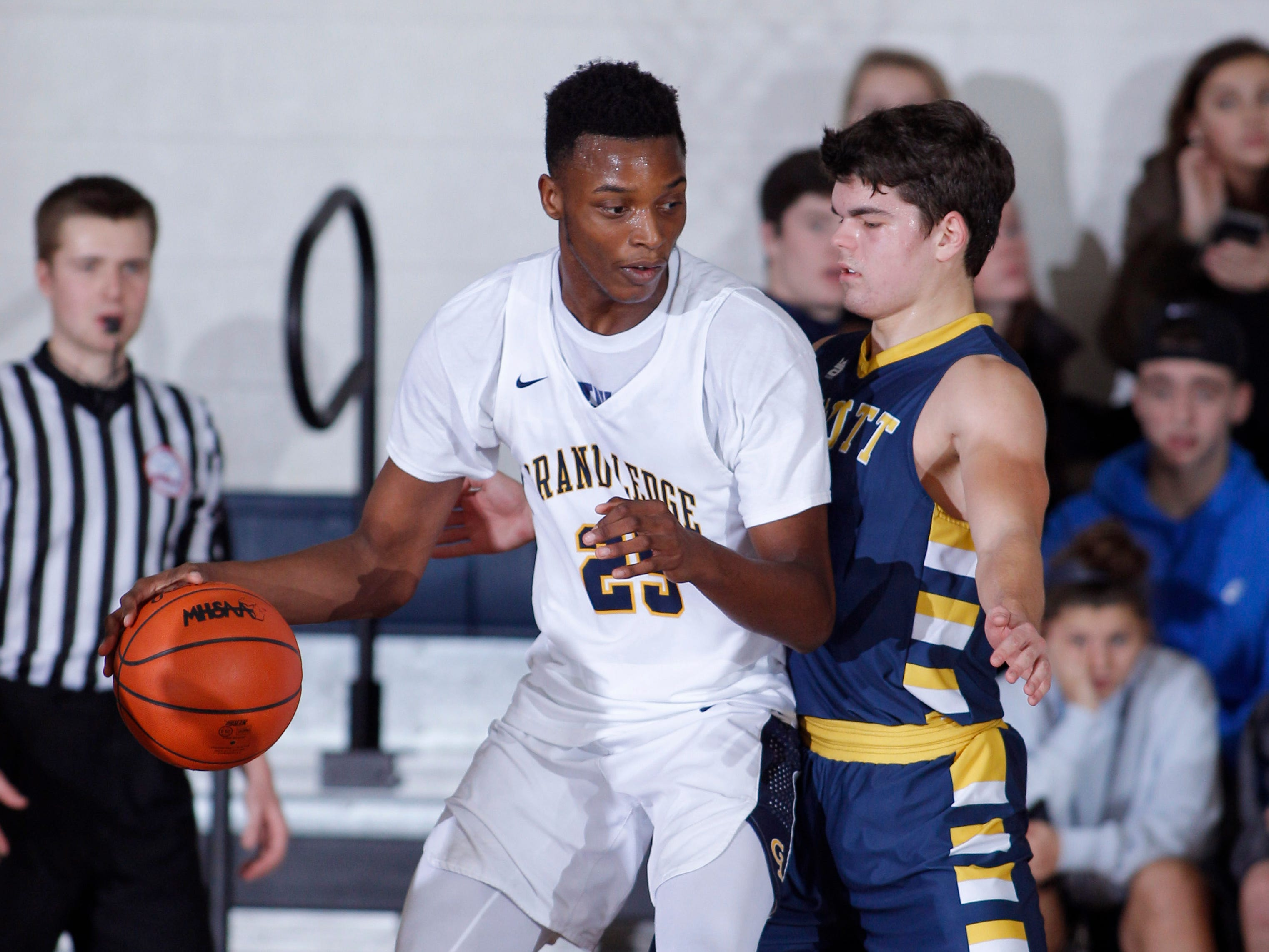Grand Ledge's Javel Lewis, left, works against DeWitt's Isaac Hungerford, Tuesday, Jan. 15, 2019, in Grand Ledge, Mich.