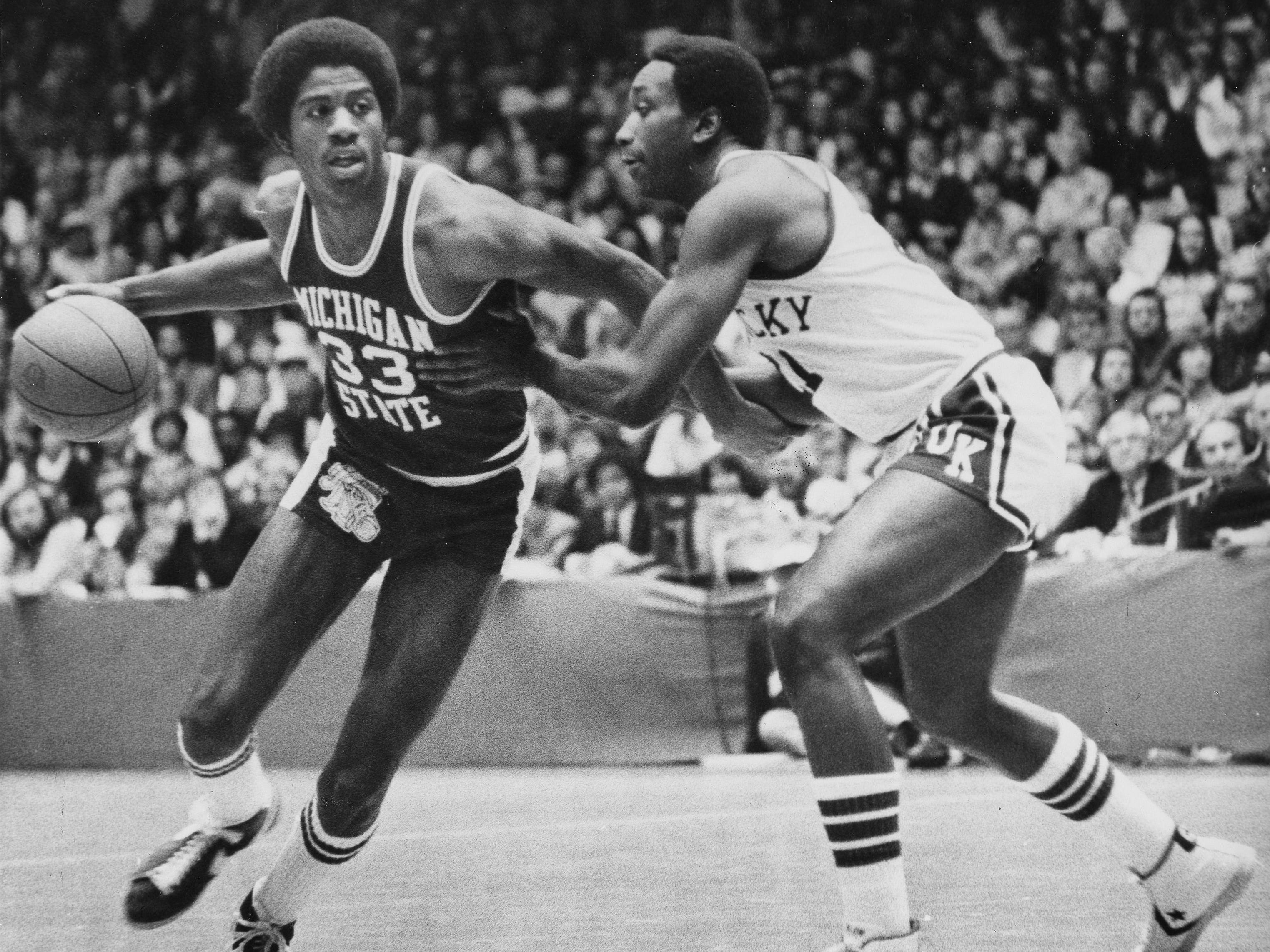 Michigan State forward Earvin Johnson (33) pushes off Kentucky forward Jack Givens as he drives for the basket in the first half of the NCAA Mideast Regional final in Dayton, Ohio, March 18, 1978.