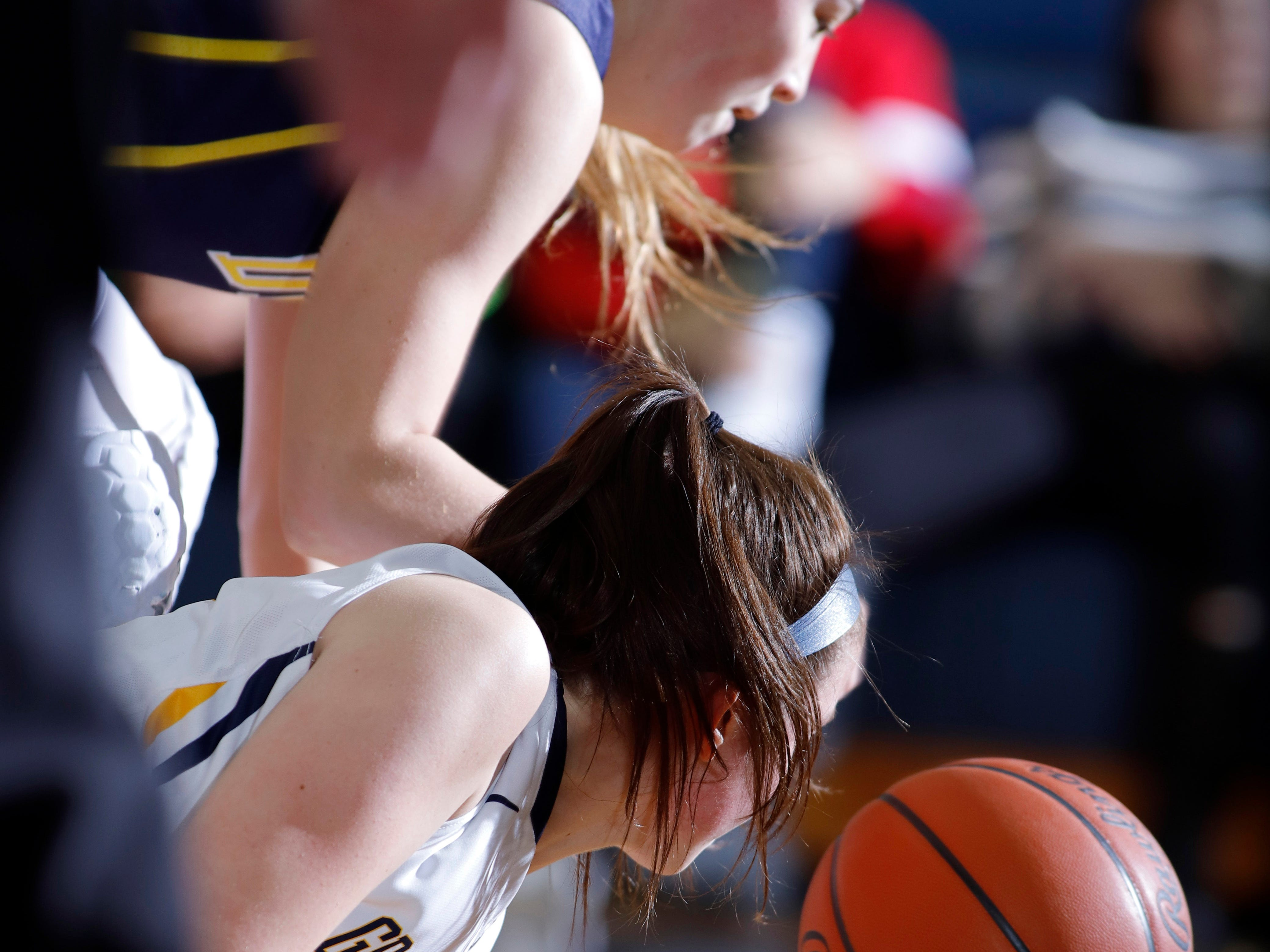 DeWitt's Maddie Petersen, top, and Grand Ledge's Kylee Pier dive for the ball, Tuesday, Jan. 15, 2019, in Grand Ledge, Mich.