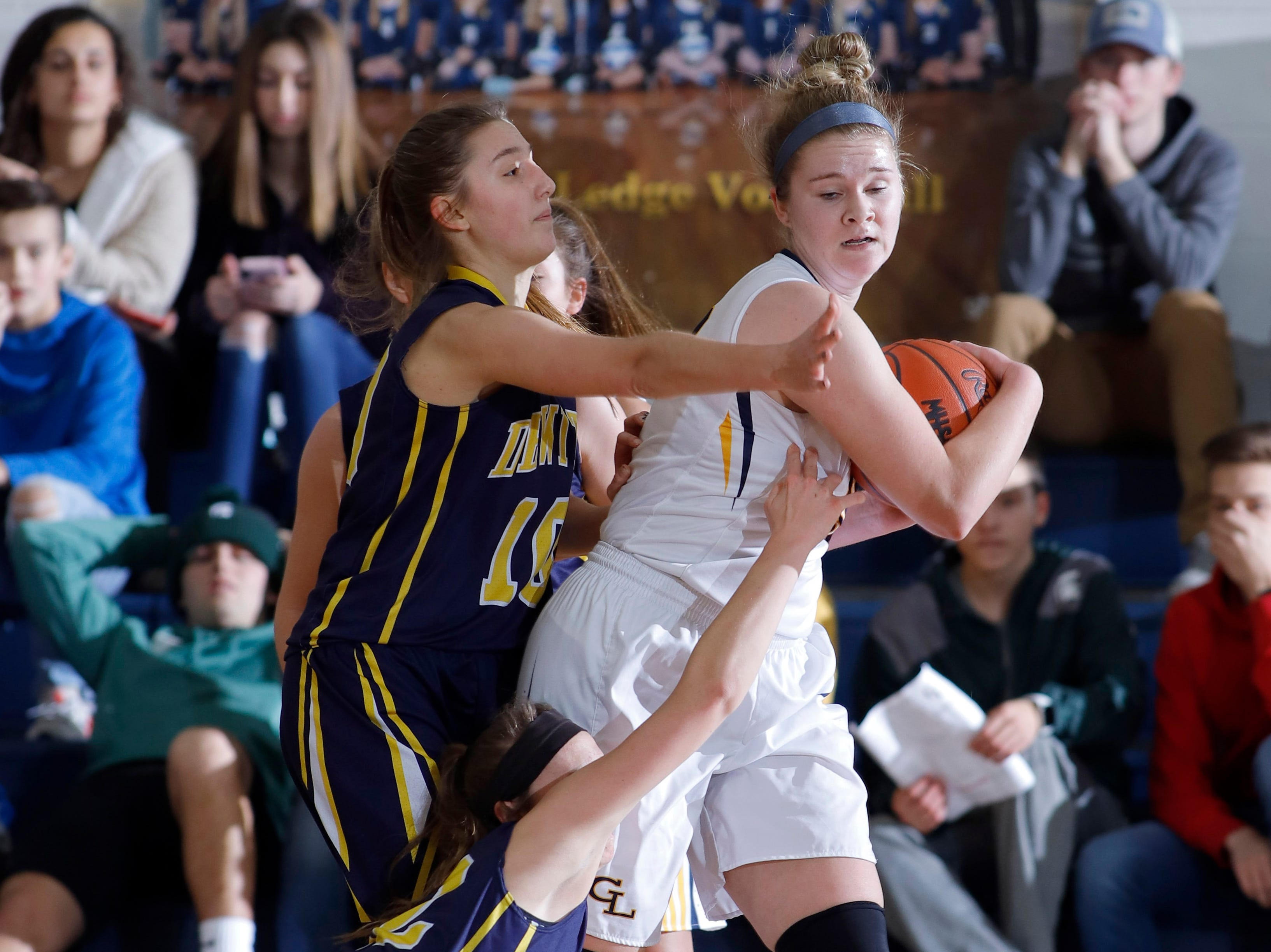 Grand Ledge's Courtney Sharland, right, is pressured by DeWitt's Sydney Mills, left, and Maddie Petersen, bottom, Tuesday, Jan. 15, 2019, in Grand Ledge, Mich.