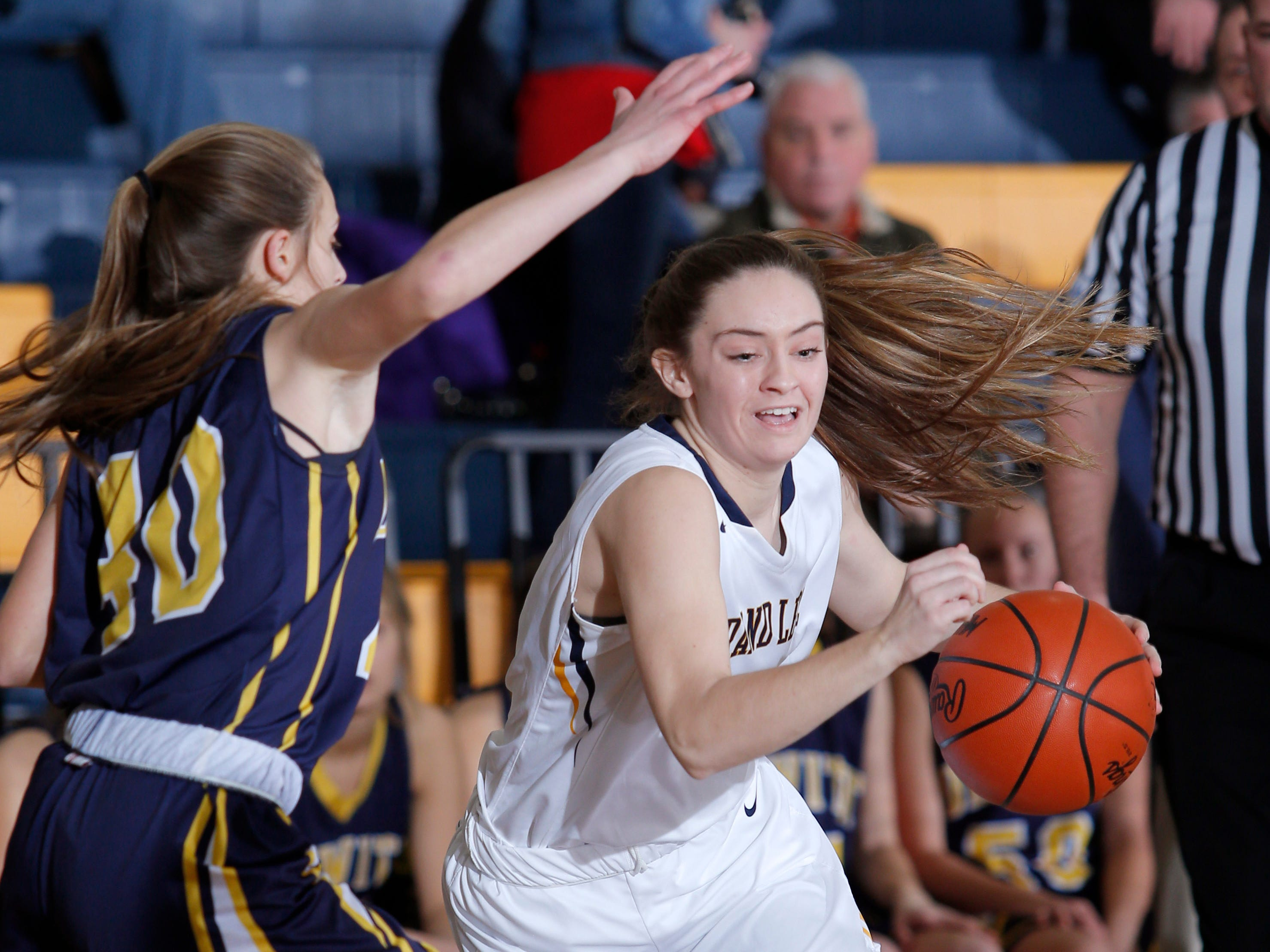 Grand Ledge's Makenzie Todd, right, drives DeWitt's Isabelle Gilmore, Tuesday, Jan. 15, 2019, in Grand Ledge, Mich.