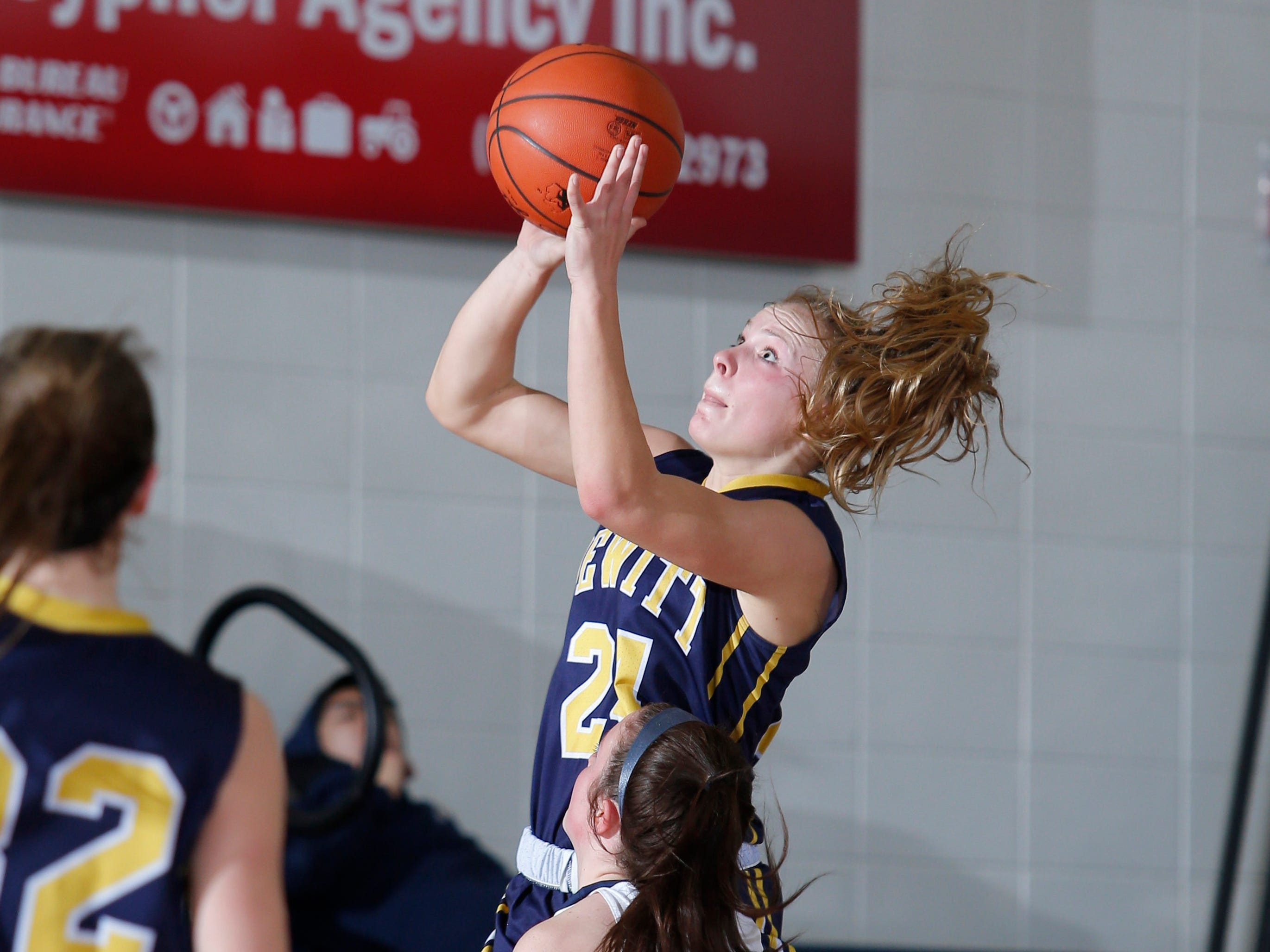 DeWitt's Annie McIntosh puts up a driving shot against Grand Ledge's Kylee Pier (12), Tuesday, Jan. 15, 2019, in Grand Ledge, Mich.