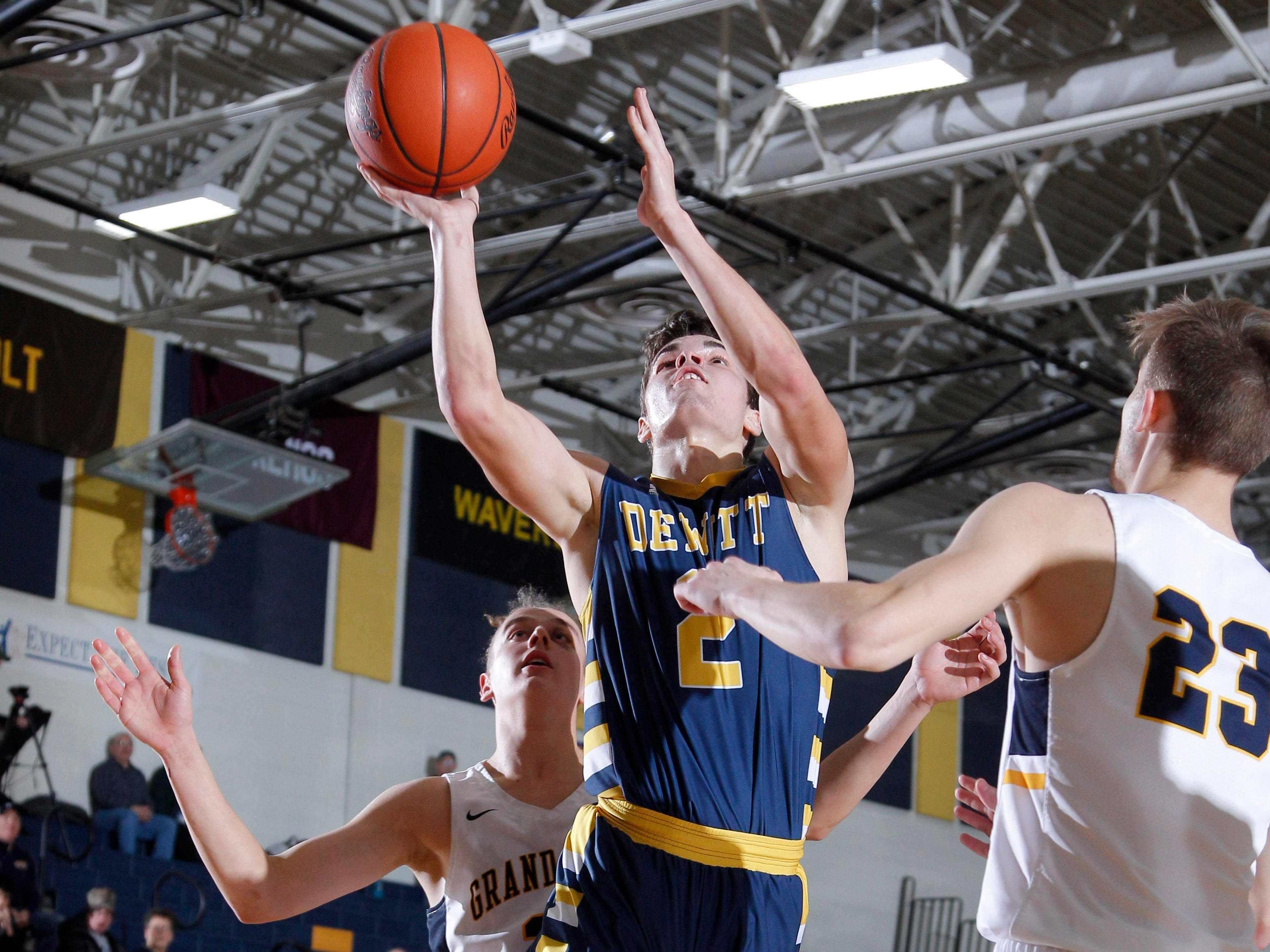 DeWitt's Isaac Hungerford, center, puts up a shot against Grand Ledge's William Jerzak, right, and Devin Gardella, Tuesday, Jan. 15, 2019, in Grand Ledge, Mich.