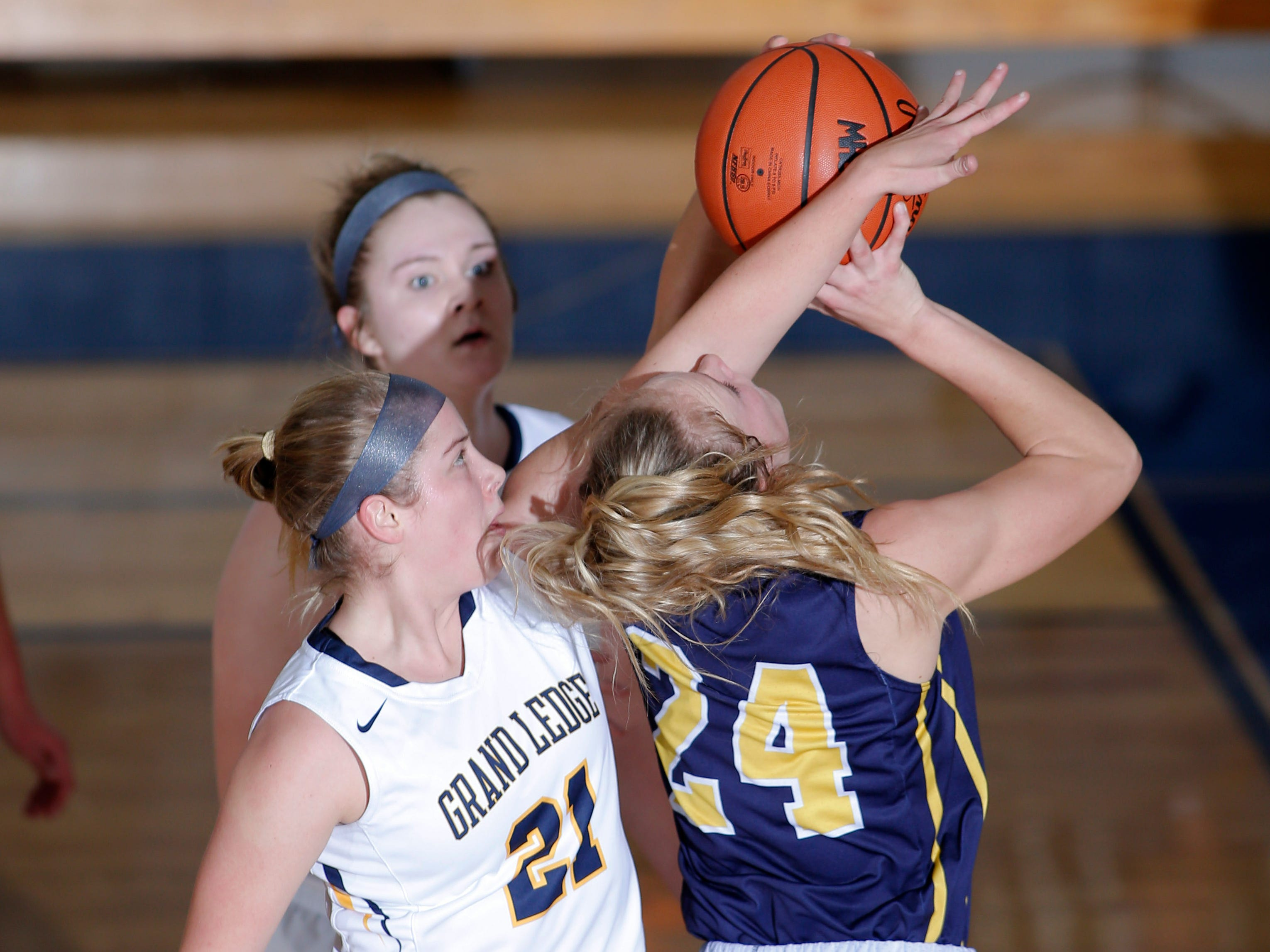 Grand Ledge's Taylor Piper (21) and Courtney Sharland, rear, defend DeWitt's Annie McIntosh (24), Tuesday, Jan. 15, 2019, in Grand Ledge, Mich.