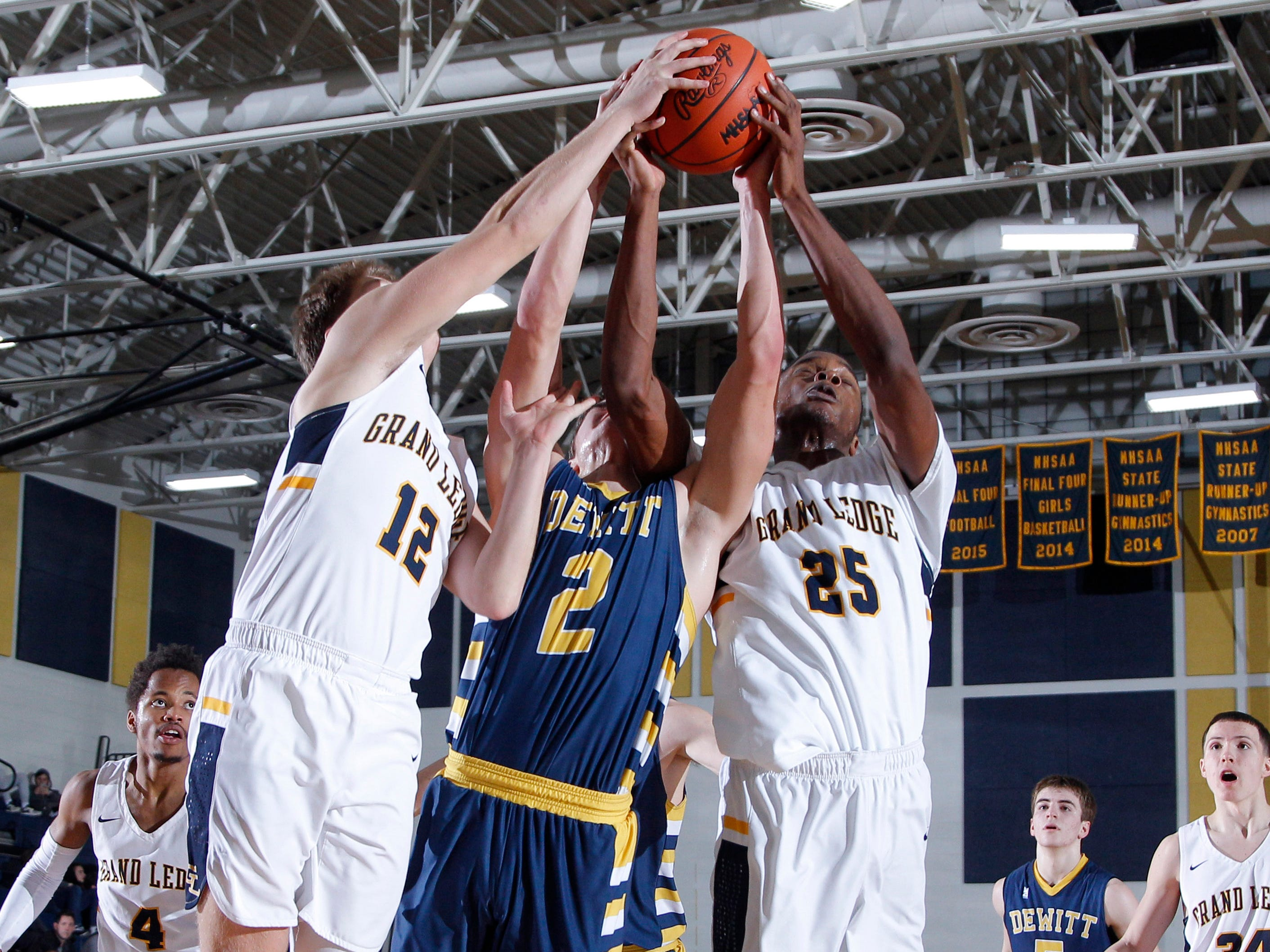 Grand Ledge's Javel Lewis, right, and Trever Rogers, left, and DeWitt's Isaac Hungerford vie for a rebound, Tuesday, Jan. 15, 2019, in Grand Ledge, Mich.