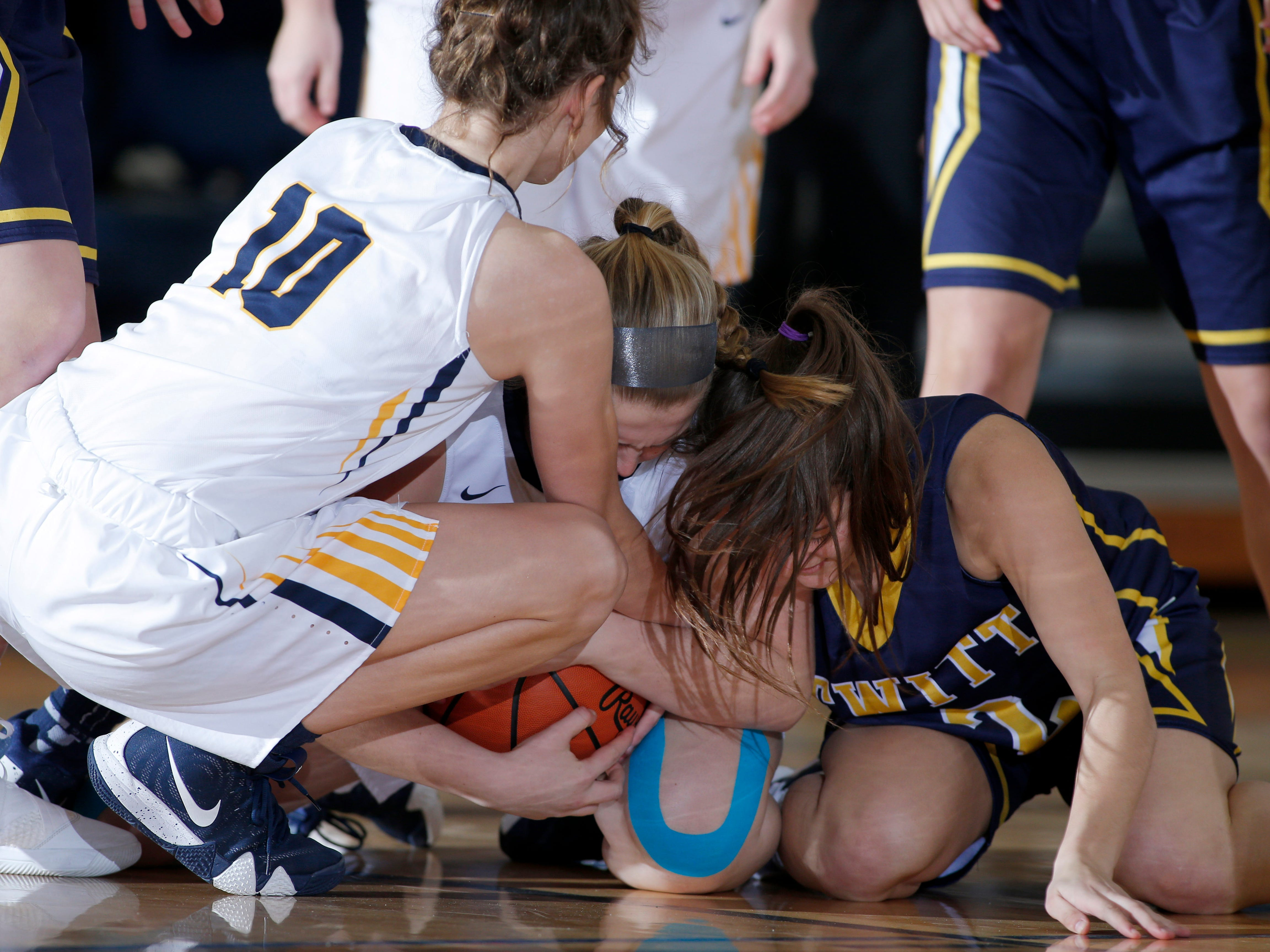 Grand Ledge's Shaelyn Sage, center, and Ali Spalding, left, and DeWitt's Olivia Reid, right, wrestle for the ball, Tuesday, Jan. 15, 2019, in Grand Ledge, Mich.