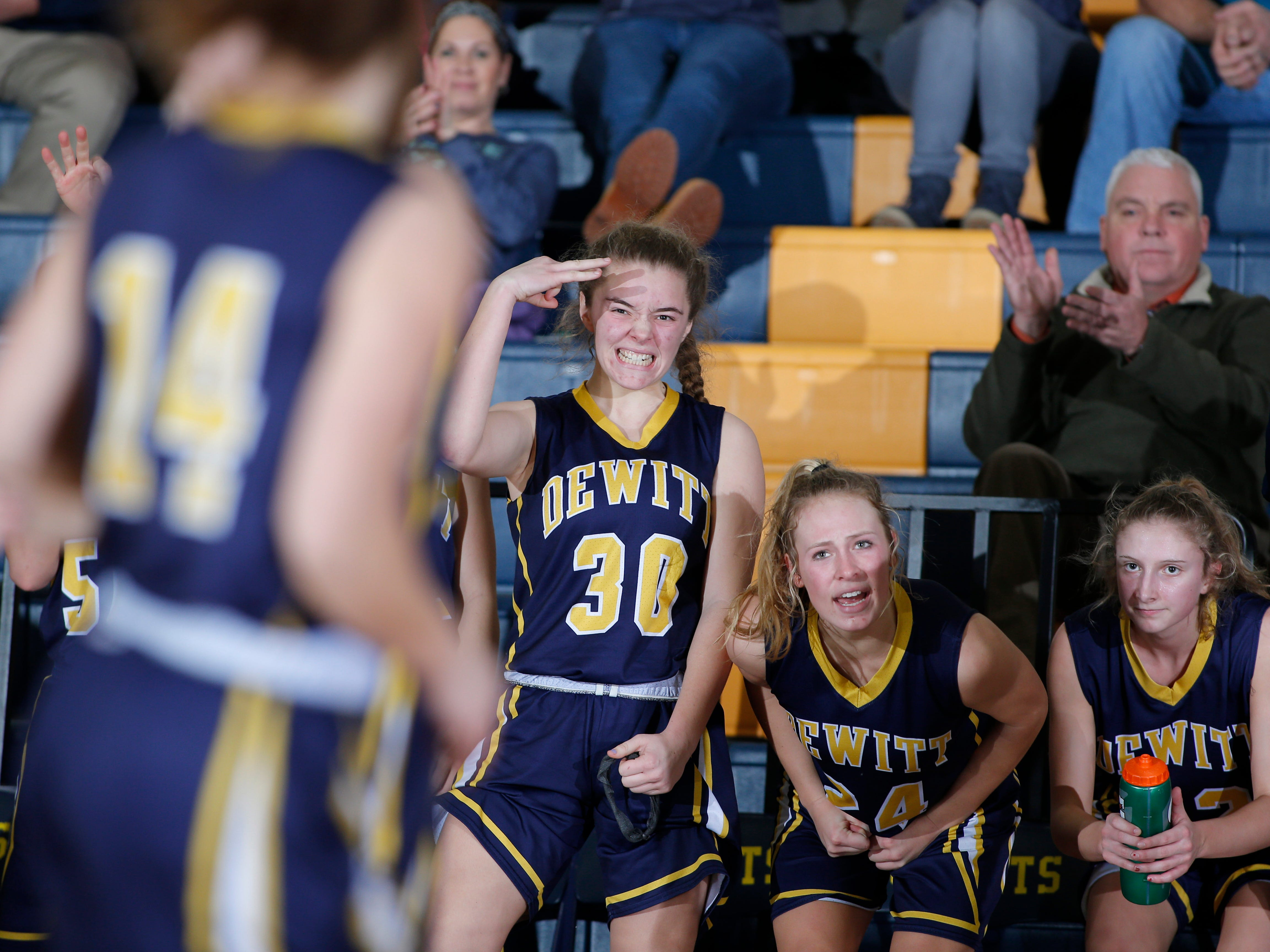 DeWitt starters on the bench, including Lily Stephan (30) and Annie McIntosh celebrate a play by reserves against Grand Ledge, Tuesday, Jan. 15, 2019, in Grand Ledge, Mich.