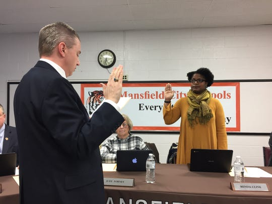 Mansfield City Schools treasurer Robert Kuehnle swears in board president Renda Cline at Tuesday's meeting.