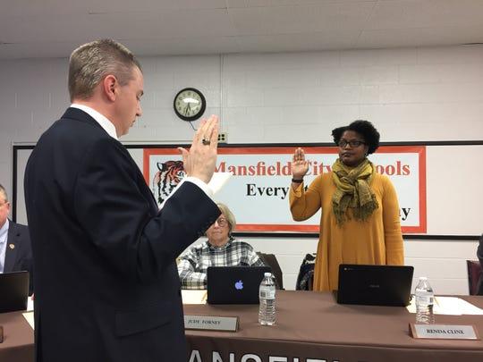 Mansfield City Schools treasurer Robert Kuehnle swears in board president Renda Cline at Tuesday's meeting.