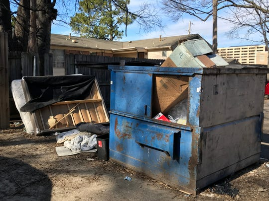 A dumpster sits open and overflowing with garbage outside a midtown apartment complex. Experts say improper garbage management is a key cause of rat problems.