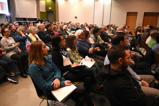 Audience members listen and take notes as Dr. Bill Mitsch speaks to a capacity crowd at the Naples Botanical Garden's Kapnick Center on Jan. 10, on red tide outbreaks' causes and possible mitigation. Red tide has caused great concern in Southwest Florida, as the algae blooms have brought fish kills and affected tourism.