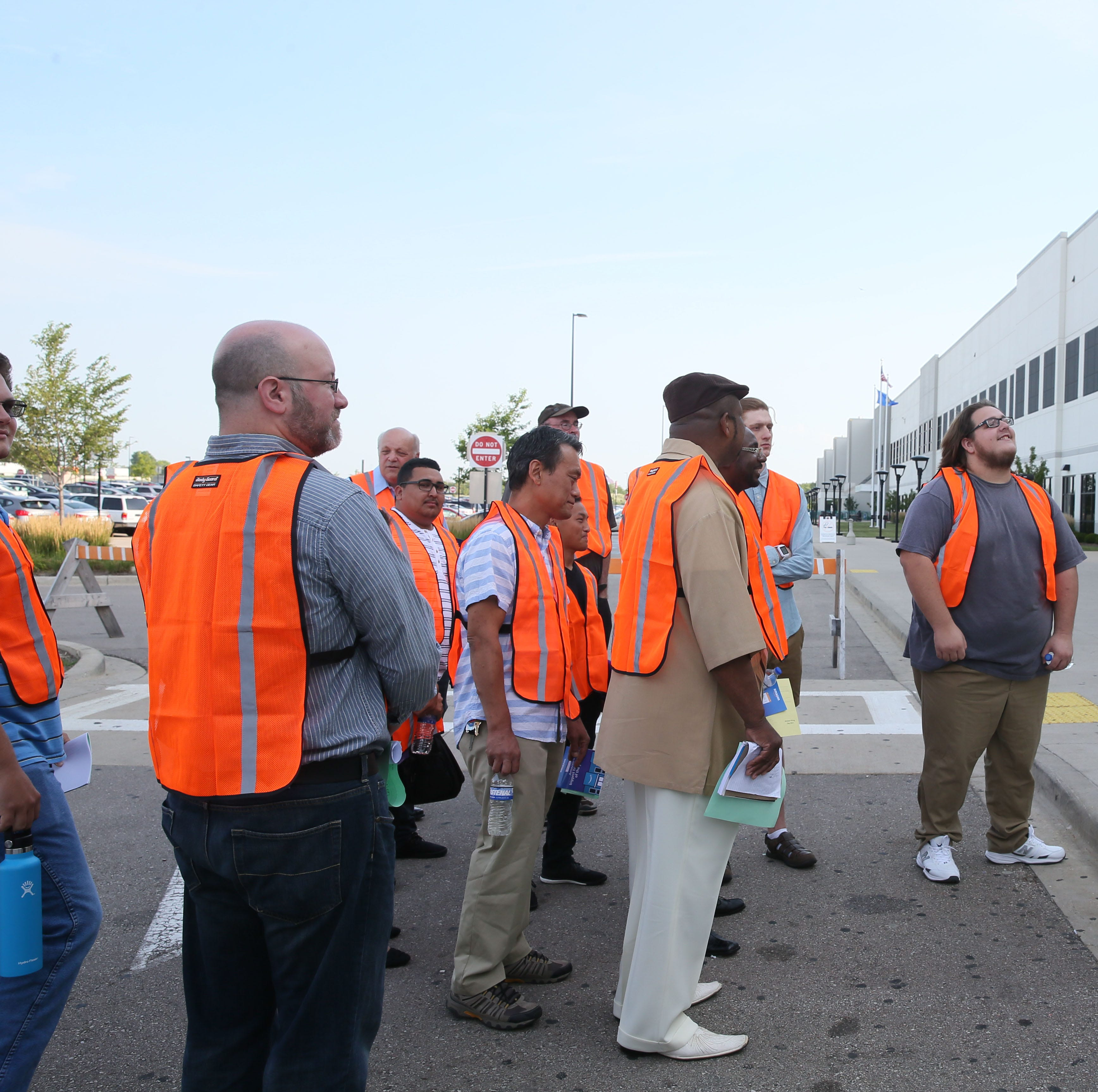 Amazon trainer Mike Fina (right) prepares to lead a group of job applicants through the company's Kenosha fulfillment center in this Aug. 2, 2017, photo.