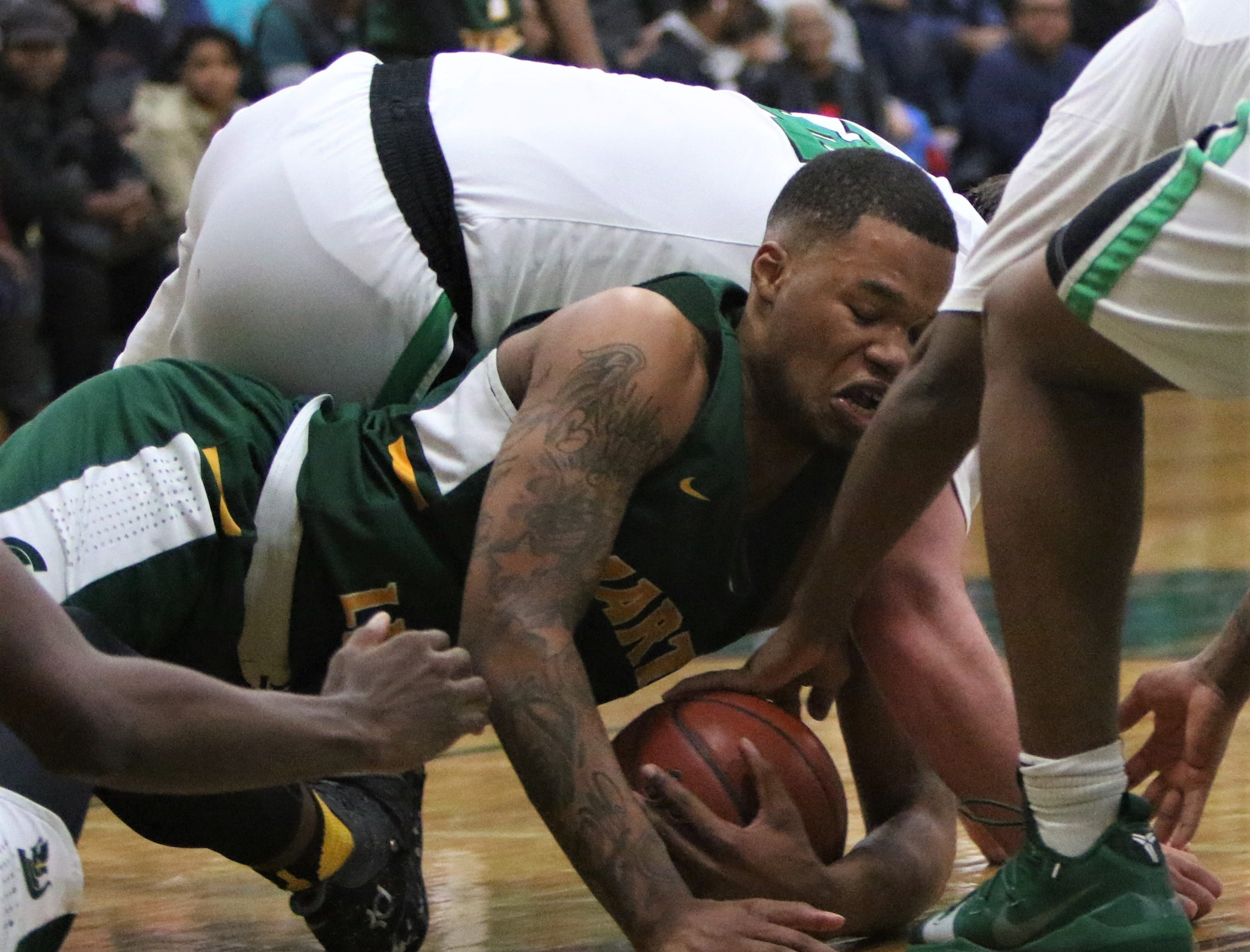 Martin Luther forward Shaun Harrison dives to corral a loose ball while surrounded by a pack of Dominican players on Jan. 15, 2019.