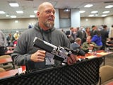 Will Murphy, president of Gun Guardian, talks about an AR-15 rifle with a prototype trigger shield during the Firearm Safety Expo.