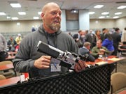 Will Murphy, president of Gun Guardian, talks Wednesday about an AR-15 rifle with a prototype trigger shield during the Firearm Safety Expo at Milwaukee Area Technical College's Oak Creek Campus. The event, hosted by Common Ground, focused on the emerging field of gun-related safety technology.