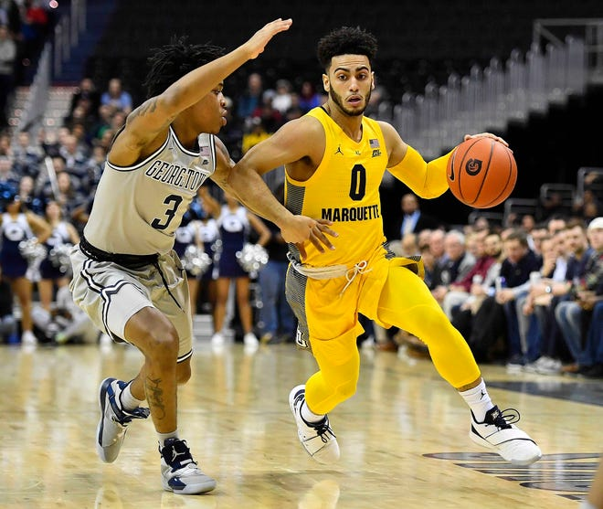 Marquette's Markus Howard dribbles past Georgetown  guard James Akinjo. Howard left with a back injury.