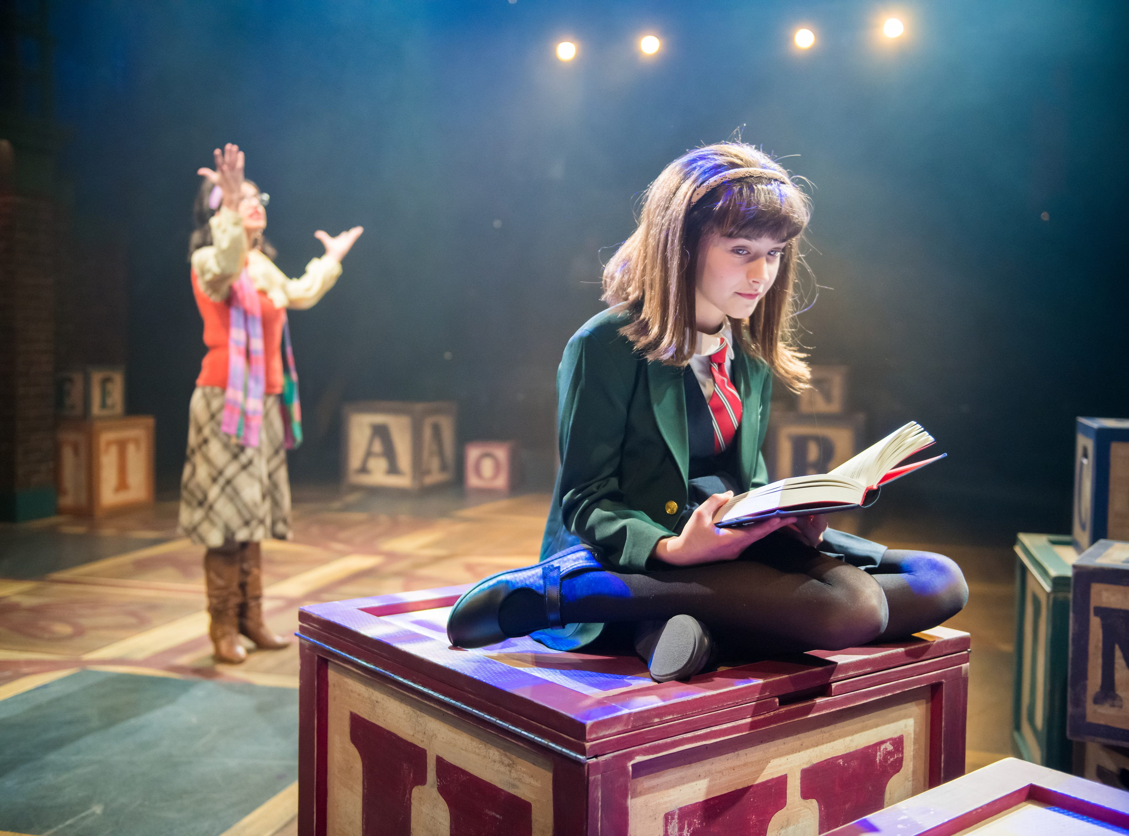 """Marina Evans (foreground) plays a girl who loves to read in First Stage's """"Matilda."""""""