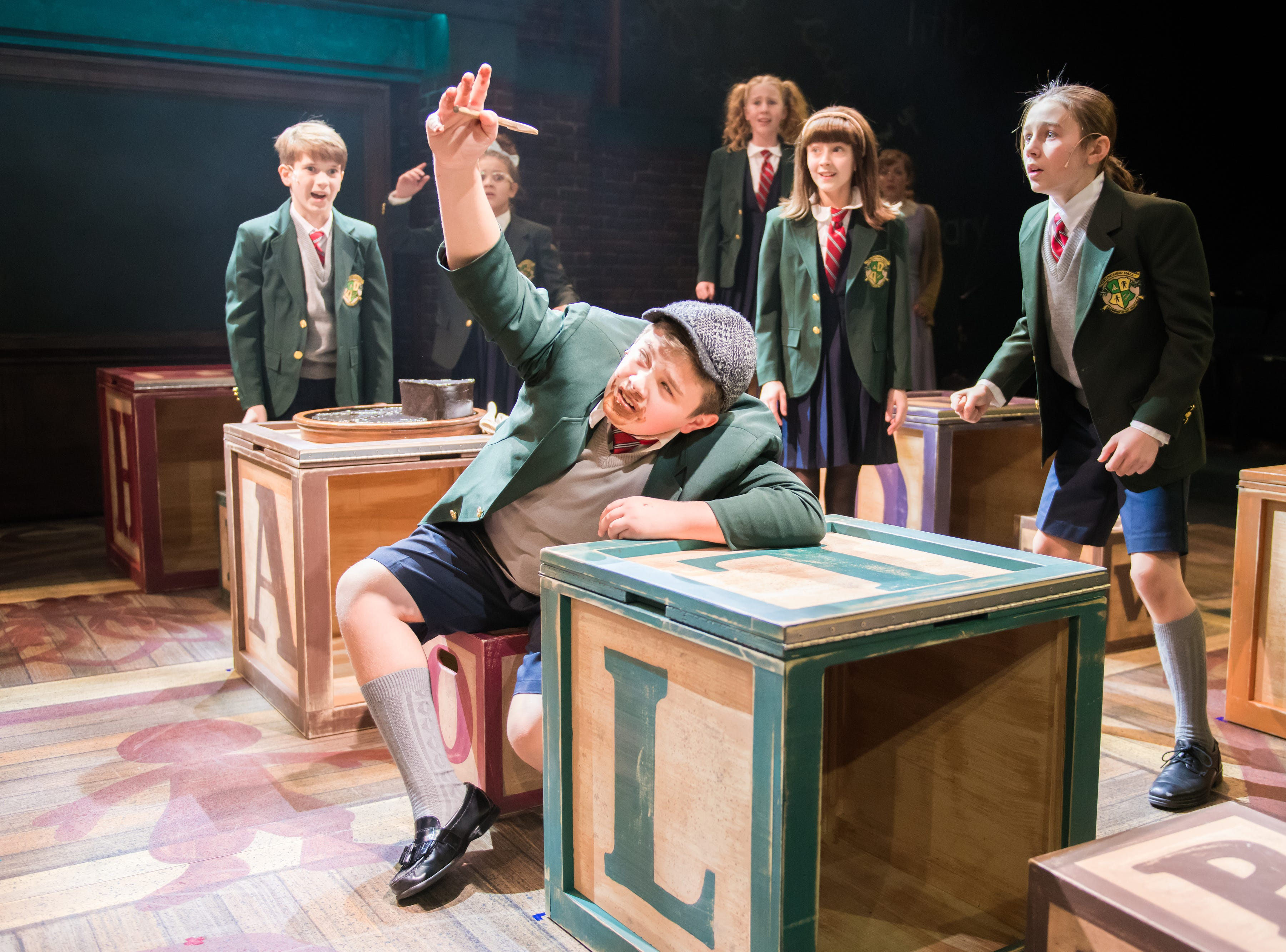 """Max Larson battles an enormous chocolate cake in First Stage's """"Matilda."""""""