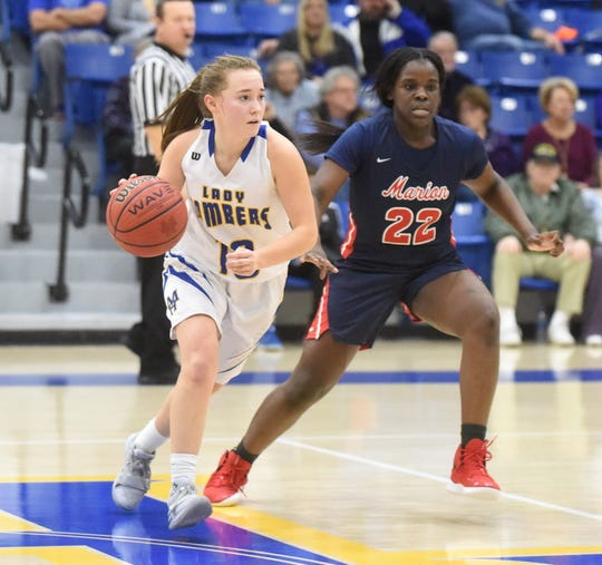 Mountain Home's Payton Huskey dribbles past Marion's Santia Robinson during the Lady Bombers' 45-30 victory Tuesday night.