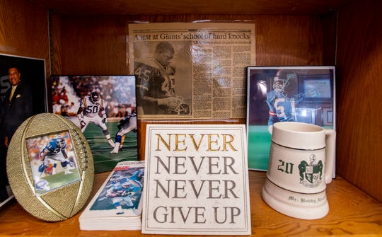Memorabilia from Jeff Davis High School Principal Bobby Abrams' pro football career sits on the shelves of his office at the school in Montgomery, Ala., on Wednesday January 16, 2019.