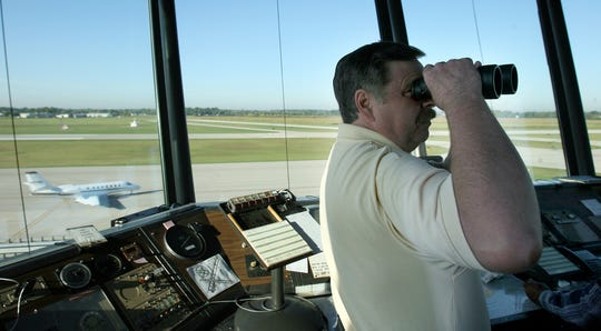 John Farratt looks out for a small plane in the area as a corporate jet taxis to the runway for takeoff at the Muncie Airport in 2009.