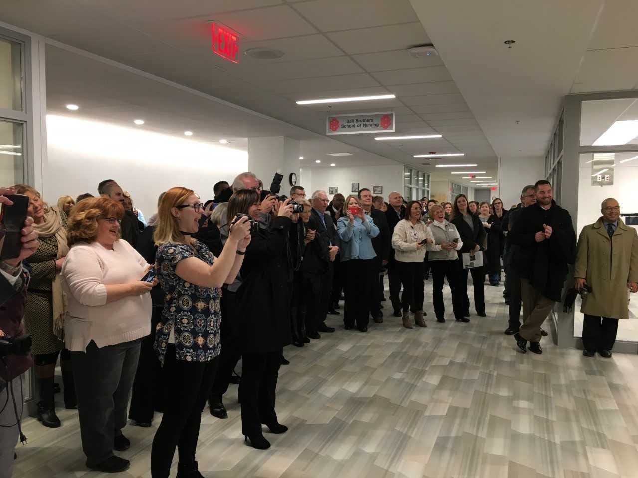 The crowd takes photographs of a ribbon-cutting ceremony at Ivy Tech Community College's new schools of nursing and health sciences in downtown Muncie on Tuesday.