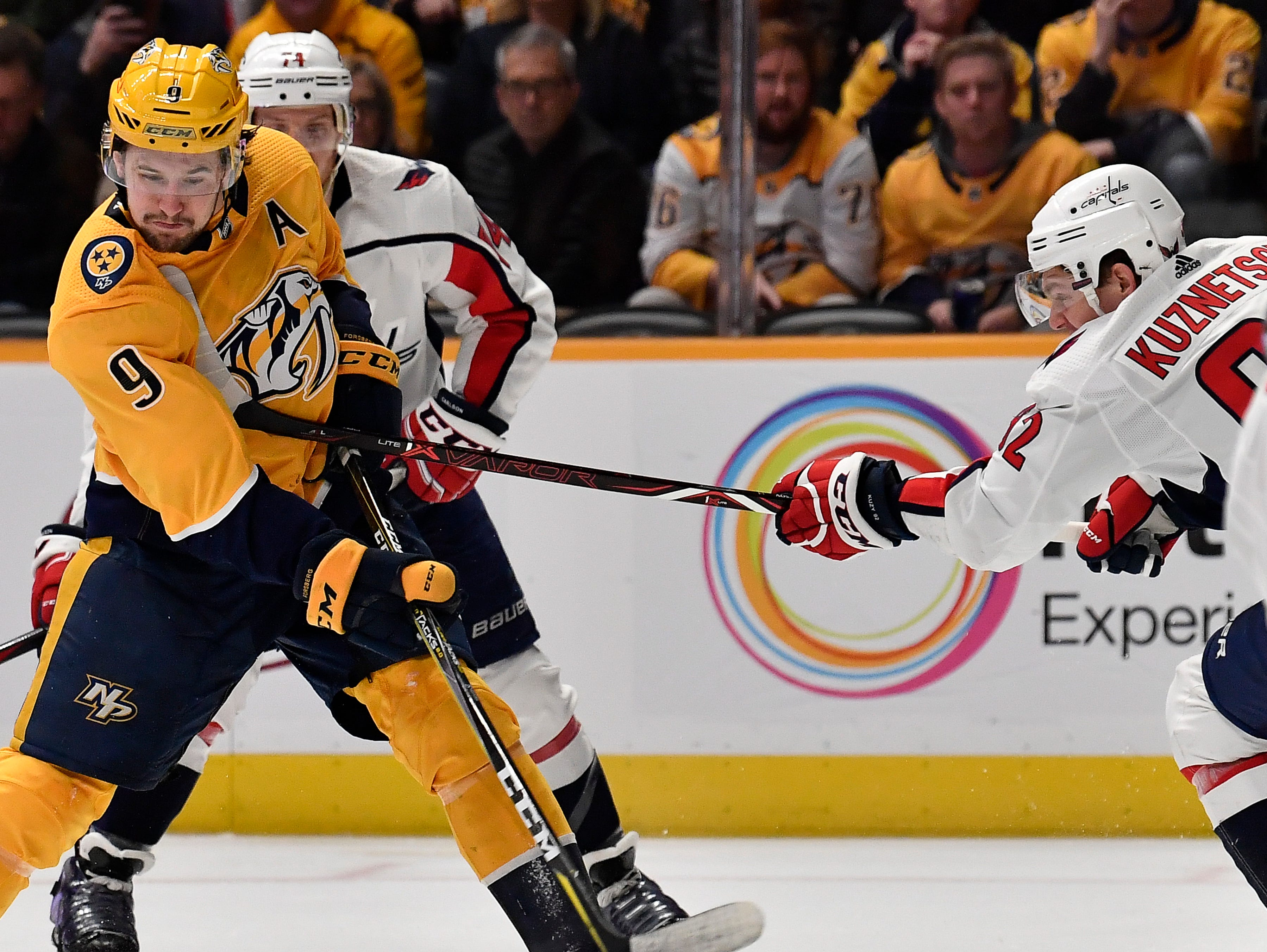 Predators left wing Filip Forsberg (9) takes a high stick from Capitals center Evgeny Kuznetsov (92) as he shoots during the third period at Bridgestone Arena Tuesday, Jan. 15, 2019, in Nashville, Tenn.