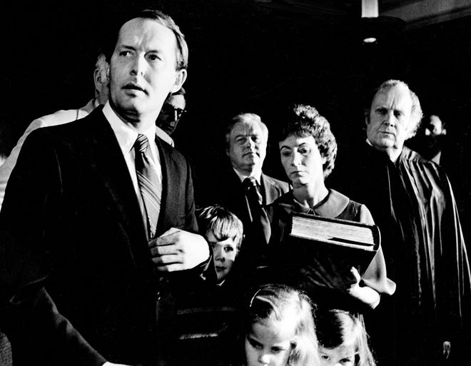 Newly sworn-in Gov. Lamar Alexander, prepares to speak to the press after being sworn in by Chief Justice Joe Henry, right, on Jan. 17, 1979. The governor's wife Honey and children, Leslee, 6, Drew, 8, and Kathryn, 4, look on.