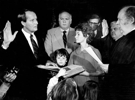 His hand resting on the 110-year-old family Bible, Gov.-elected Lamar Alexander, left, takes the oath of office from Chief Justice Joe Henry, right, four days early on Jan. 17, 1979. Alexander's wife Honey holds the Bible as children Drew and Leslee place their hands on the pages as House Speaker Ned McWherter, Attorney General William Leech and Secretary of State Gentry Crowell watch.