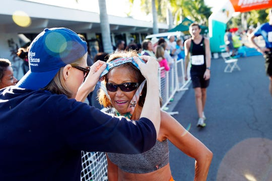 Jeannie Rice, a part-time resident of Bonita Springs, gets her medal after finishing the 2015 Naples Daily News Half Marathon. Rice, 71, recently broke her own world record for the fastest marathon by a woman age 70 or older.