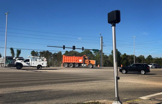 An orange construction dump truck turns left to travel north on U.S. 41 at the intersection with Estero Parkway in Estero on Jan. 16, 2019.