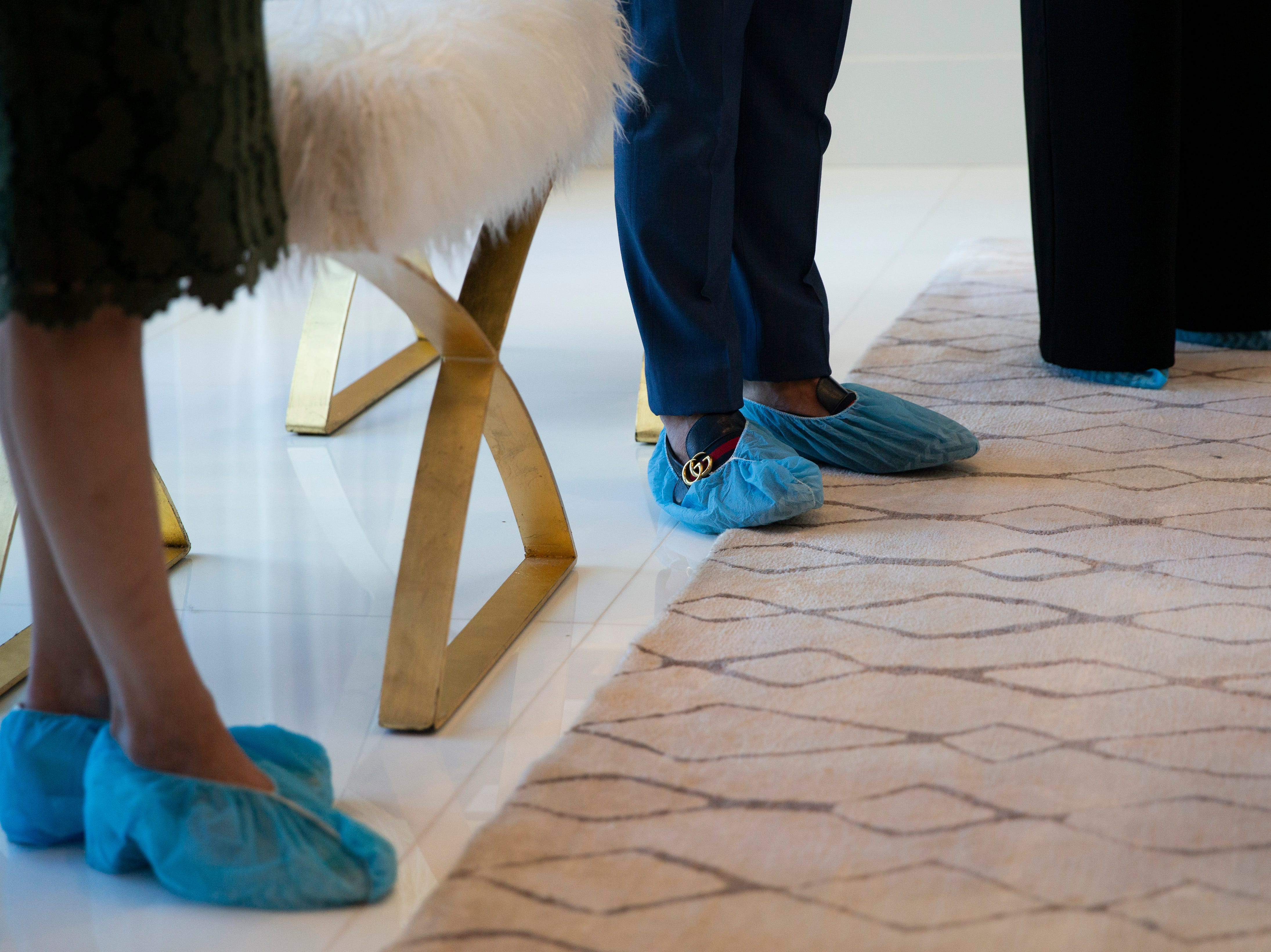 From left to right, home designer Brenda Canada and interior designers Wilfredo Emanuel and Ashton Reams speak to guests during the 7th annual Kitchen Tour, hosted by the Naples Woman's Club in Naples on Wednesday, January 16, 2019. All attendees were asked to wear protective covers over their shoes before entering each home.