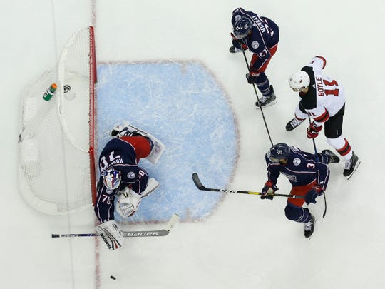 Columbus Blue Jackets' Joonas Korpisalo, left, of Finland, makes a save as teammates Ryan Murray, top, Seth Jones, bottom, and New Jersey Devils' Brian Boyle look for the rebound during the first period of an NHL hockey game Tuesday, Jan. 15, 2019, in Columbus, Ohio.