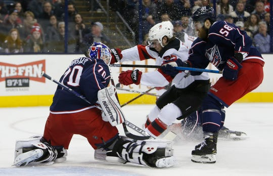 Columbus Blue Jackets' Joonas Korpisalo, left, of Finland, makes a save as teammate David Savard, right, and New Jersey Devils' Pavel Zacha, of the Czech Republic, fight for position during the first period of an NHL hockey game Tuesday, Jan. 15, 2019, in Columbus, Ohio.