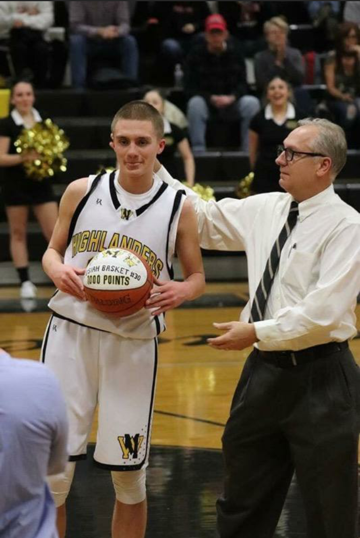 West Milford veteran boys basketball coach John Finke, right, presents senior Josiah Basket with a commemorative ball after scoring his 1,000th career point earlier this season. Finke announced his retirement this week after 30 years as the Highlanders head coach.