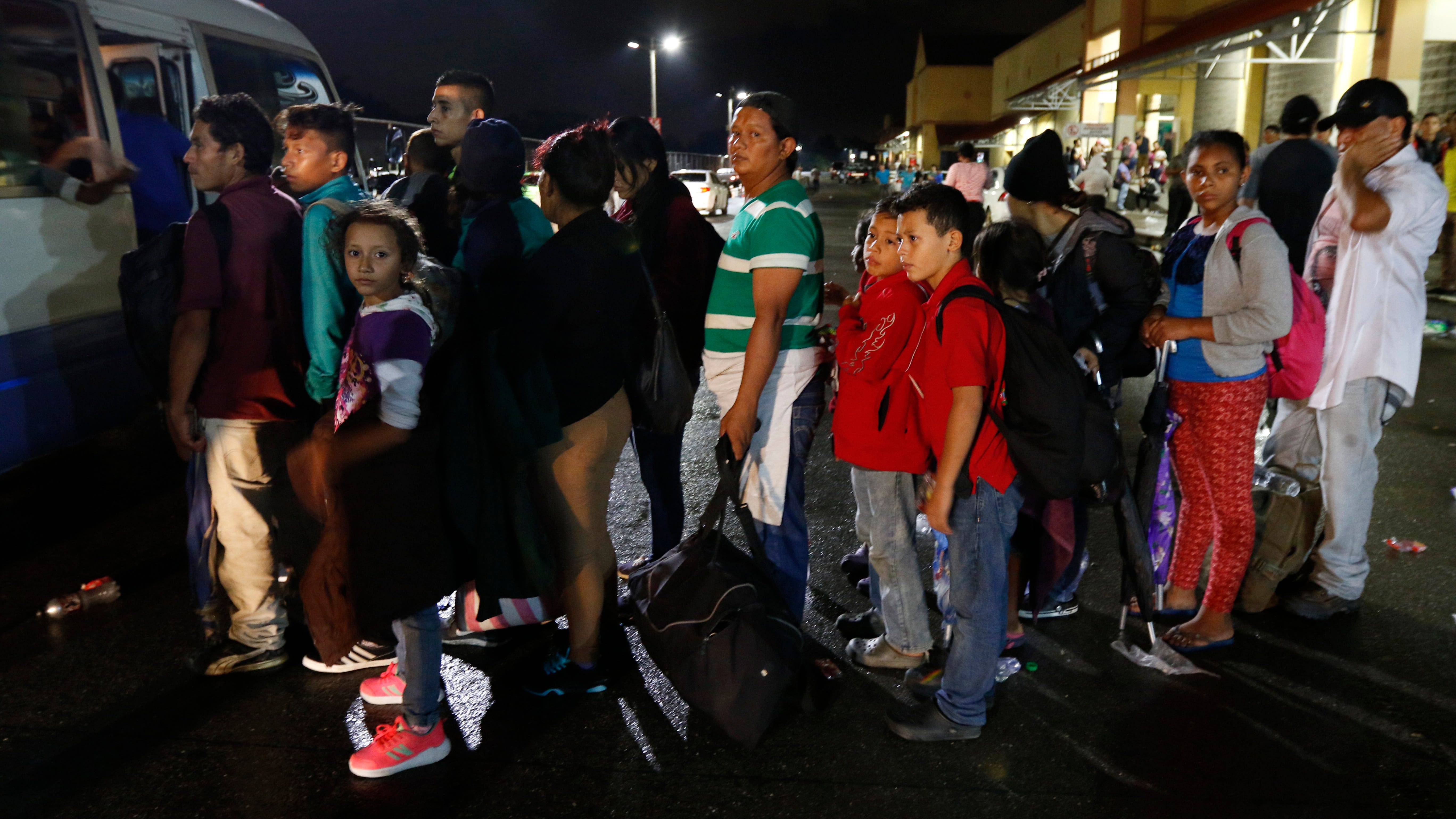 Migrants hoping to reach the U.S. wait in line to board a bus toward Honduras' border with Guatemala, as hundreds of migrants set off by bus or on foot from a main bus station in San Pedro Sula, Honduras, late Monday, Jan. 14, 2019. Yet another caravan of Central American migrants set out Monday from Honduras, seeking to reach the U.S. border following the same route followed by thousands on at least three caravans last year.