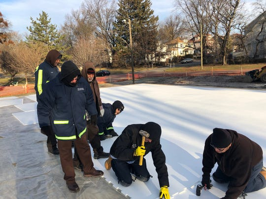 Workers assemble synthetic ice rink in Veteran's Park in Passaic on Tuesday. The assembly is complete.