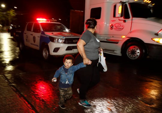 A woman and child pass a police vehicle as a caravan of several hundred migrants set off walking under a steady rain toward the distant U.S., from a main bus station in San Pedro Sula, Honduras, late Monday, Jan. 14, 2019. Yet another caravan of Central American migrants set out Monday from Honduras, seeking to reach the U.S. border, following the same route followed by thousands on at least three caravans last year.