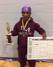 Dwight Morrow's Devin Martin holding his winning bracket from the Garfield Tournament.