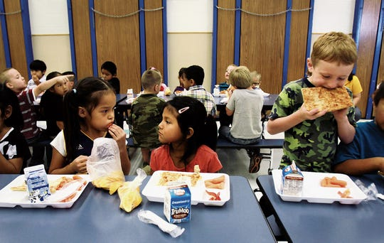 Kindergartners April Ruth Nez, 5, left, Autumn Thompson, 5, and Cooper Collom, 5, eat lunch at the Ruth M. Bond Elementary School cafeteria on Aug. 23, 2013, in Kirtland. The Central Consolidated School District spends more than $160,000 each month to provide meals to students, but it could stop being reimbursed for that amount in April if the federal government shutdown continues.