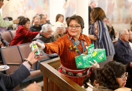 Delegate Eugenia Charles-Newton, who represents Shiprock Chapter, distributes beverages to the audience during a special session for the 24th Navajo Nation Council on Tuesday in Window Rock, Ariz.