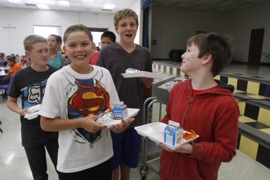 Nick Miller-Dawes, second from left, Rowan Kalmbach and Elijah Michael wait in line Aug. 14, 2014, with their school lunch at Heights Middle School in Farmington.