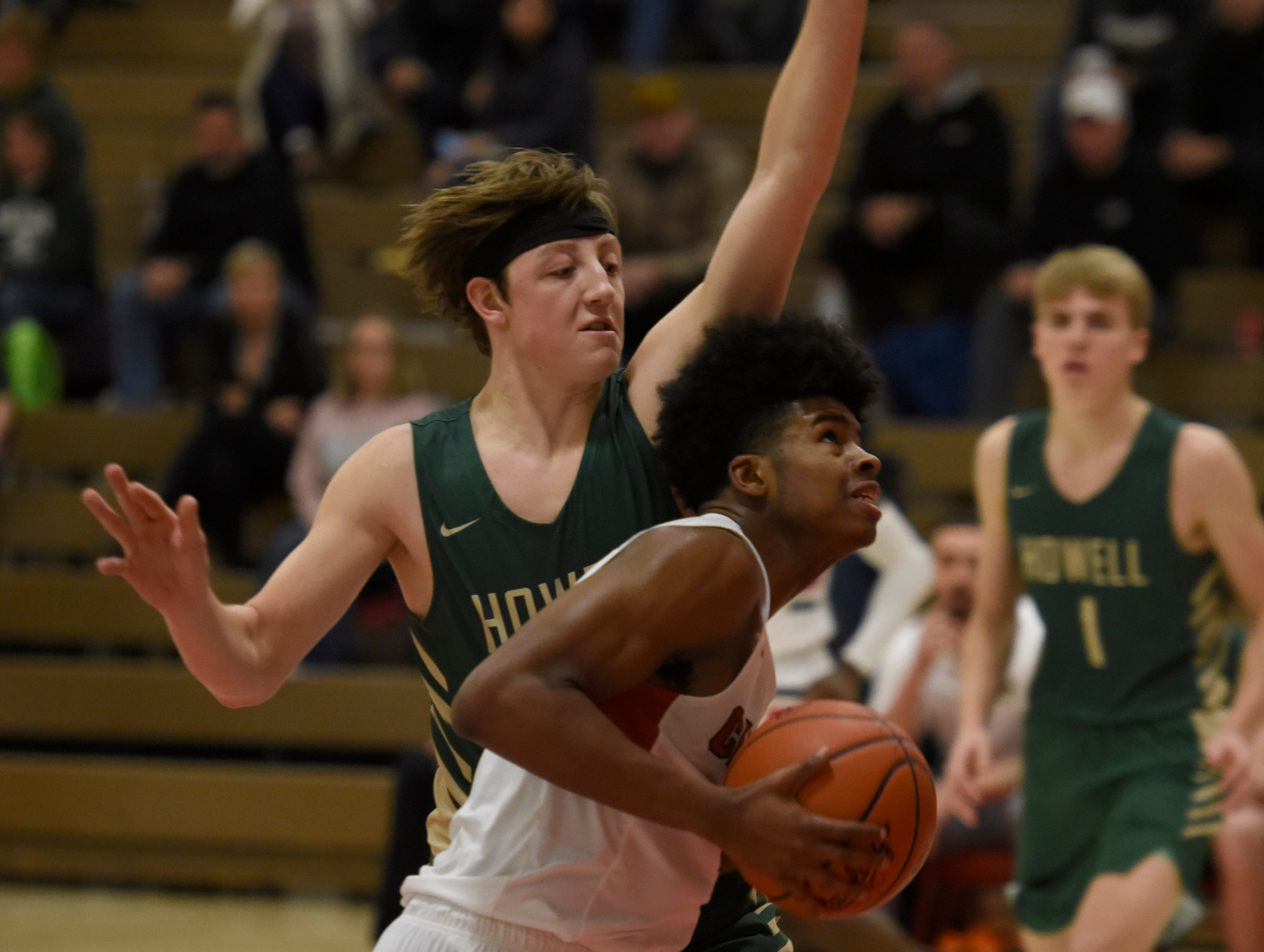 Howell's Luke Russo (2) and Canton's Kendall Perkins (1) during a KLAA match up won by Canton 74-62 played at Canton Jan. 15, 2019